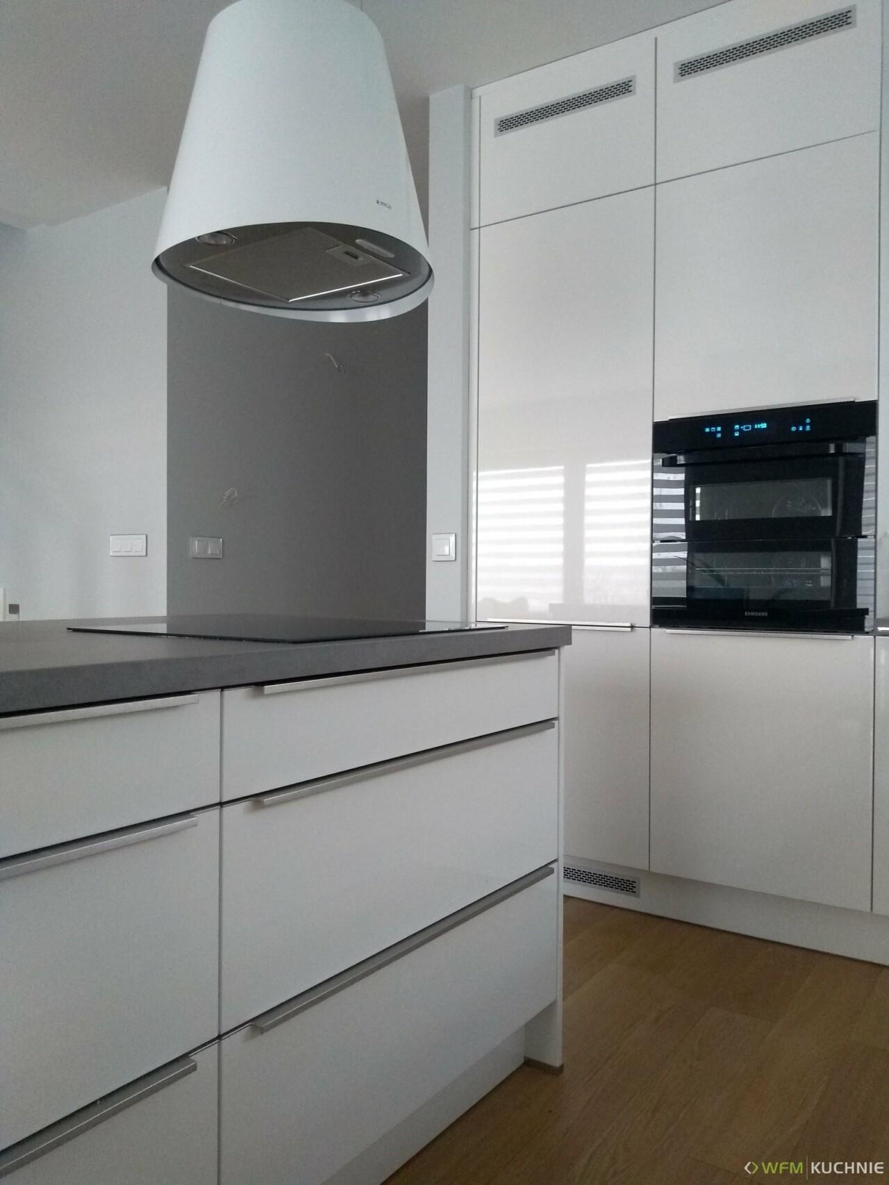Nowoczesna zabudowa kuchenna na wymiar WFM CALMA biały połysk P101 w wysokiej zabudowie z uchwytami nabijanymi szczotkowanymi oraz funkcjonalną wyspą - WFM KUCHNIE Kraków